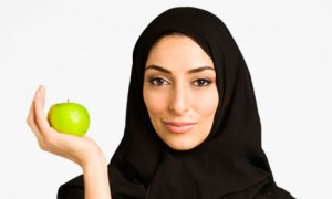 Middle Eastern woman in burkha holding apple